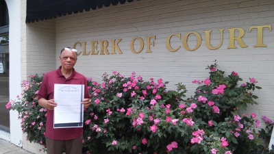 Ellis standing in front of the Clerk of Court in Clinton, LA (East Feliciana Parish)