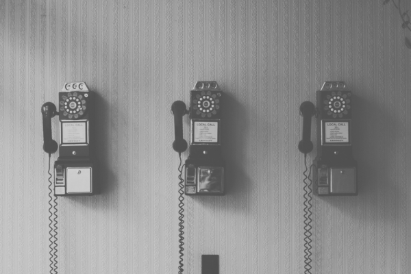 Two wall mounted telephones side by side