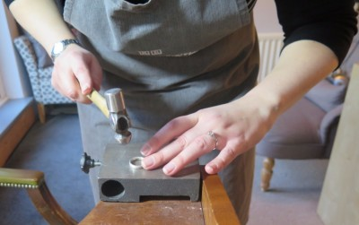 Bride-to-be using a ball hammer to texture the edges of her own platinum wedding ring during an experience day at Rosalyn's Emporium
