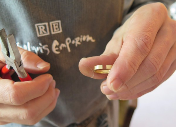 Groom holding a pair of red pliers whilst making his bride-to-be's 18ct Gold wedding ring.