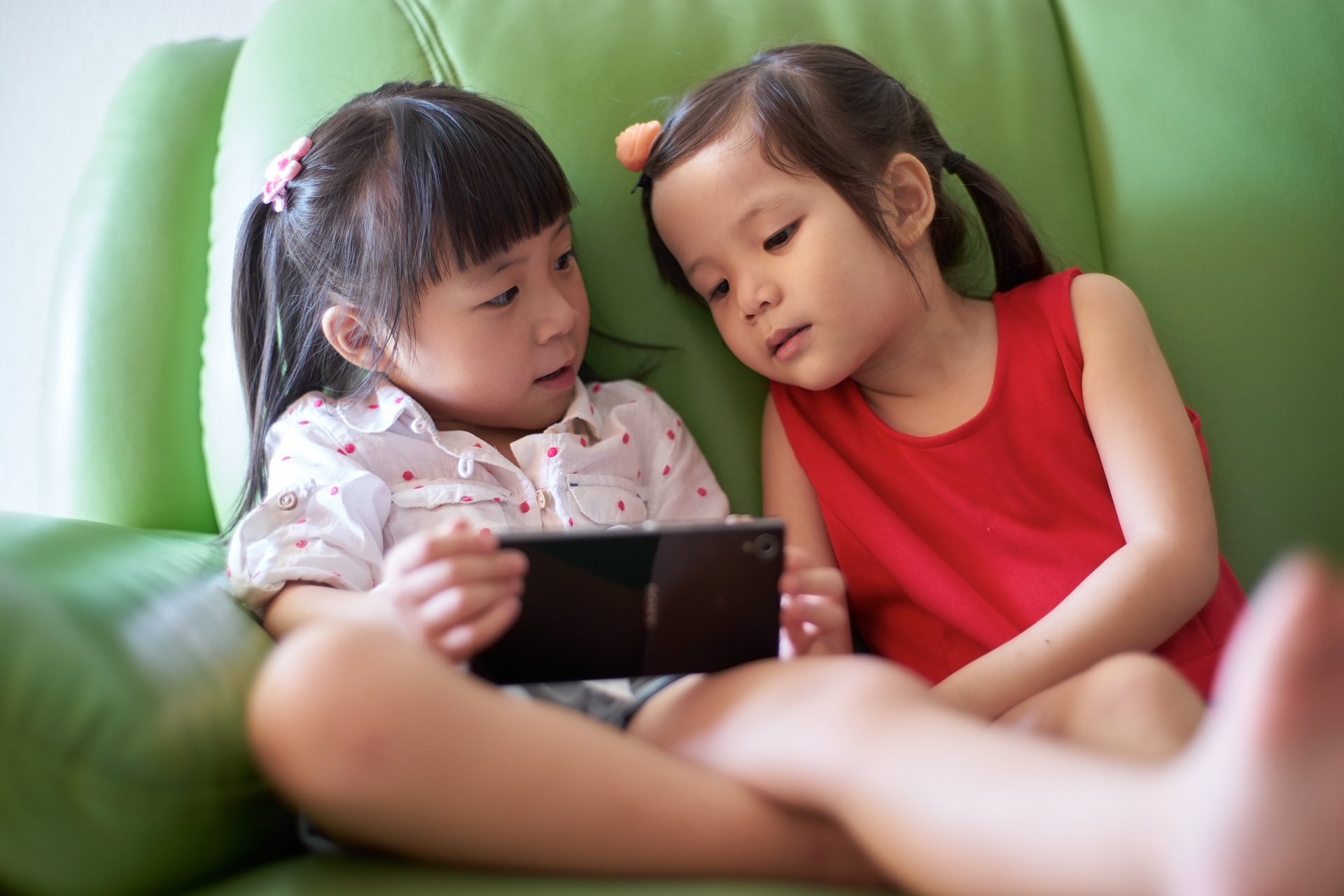 graphicstock-two-asian-girls-playing-with-smart-phone_rdIQTswgox-1