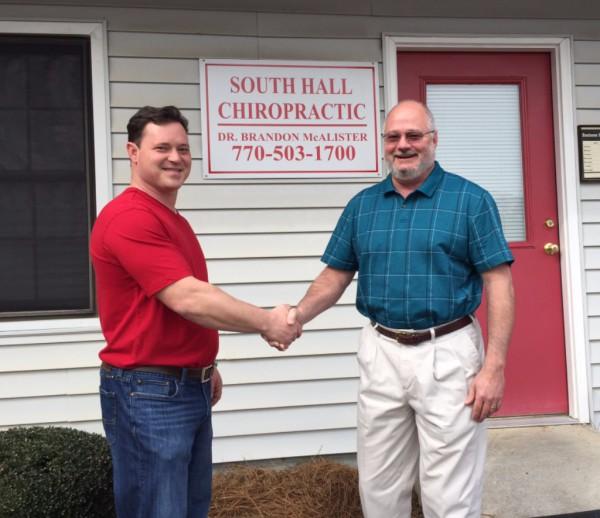 Dr. McAlister shaking Dr. Dellinger's hand