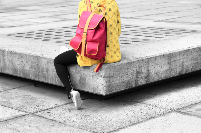 Girls sitting with fashionable backpack and yellow jumper