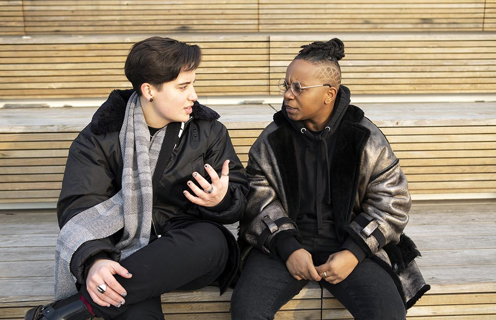 5c998a7e5b8ede1252420cce_Two-transmasculine-people-sitting-together-and-having-a-serious-conversation.jpg