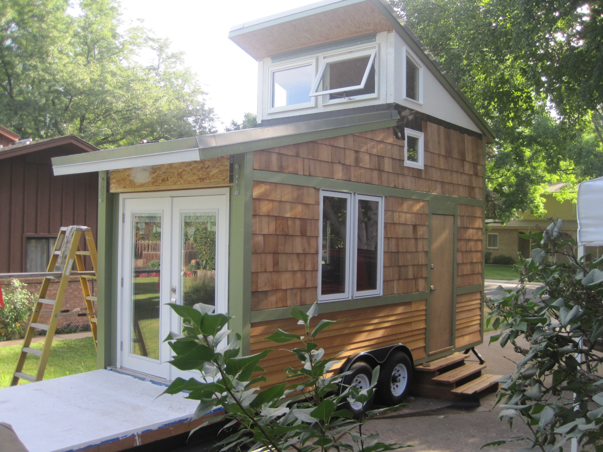 Picture of the Rear Right Corner View of the tiny house known as The Band Wagon. Showing the Deck and French Doors as well as the windows and side door.