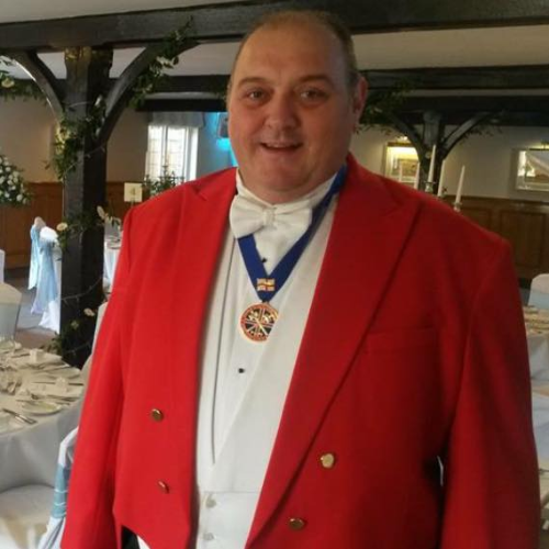 The Toastmaster, Moastmaster Nick Ede, posing in his red coat and tails at Kingswood Golf Club before the start of the wedding reception