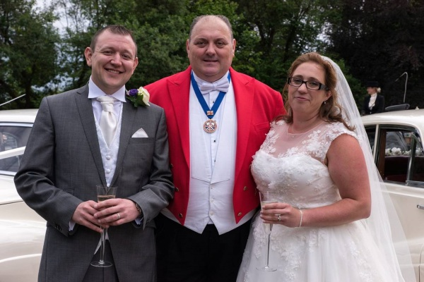 Toastmaster in his redcoat and tails posing with the Bride and Groom - happy smiles all round