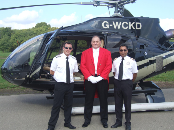 Toastmaster Nick Ede looking handsome in redcoat tails between the two helicopter pilots infront of G-WCKD