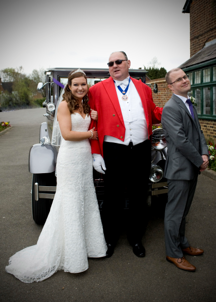 Toastmaster in dark glasses looking cool with the Bride holding his arm instead of the Groom