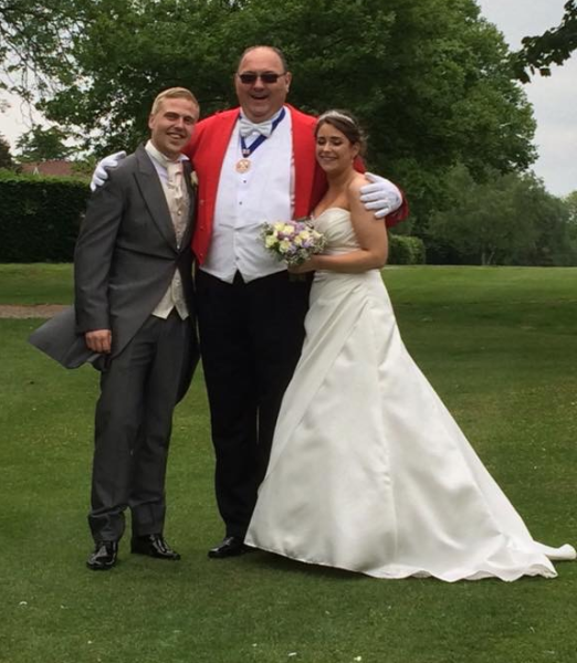 Toastmaster in dark glasses looking cool between the blushing Bride and Groom