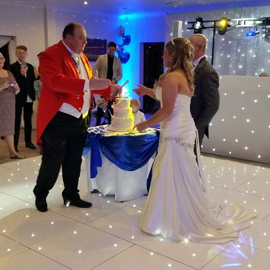 Toastmaster, Nick Ede, giving the Bride and Groom the cake knife to cut their wedding cake at their New Year's Eve Wedding Reception