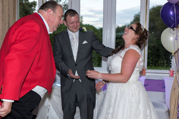 Toastmaster making Bride and Groom laughing at wedding reception