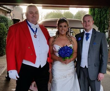 New Year Bride and Groom with Toastmaster avoiding stepping on wedding dress