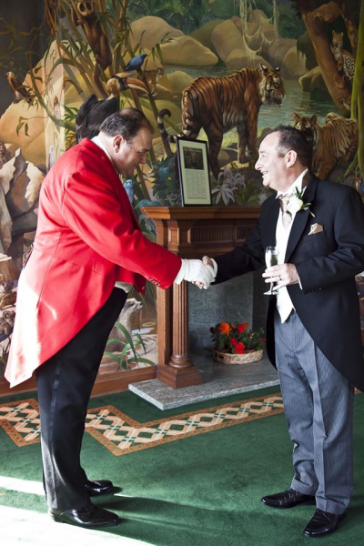 Toastmaster in red coat tails and white gloves shaking hands with the Groom and wishing him well for the future