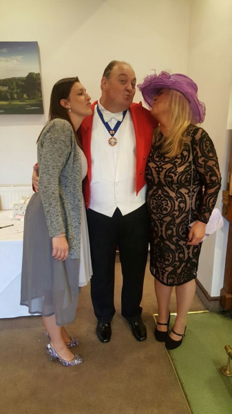 Toastmaster enjoying being smothered with kisses from the wedding guests