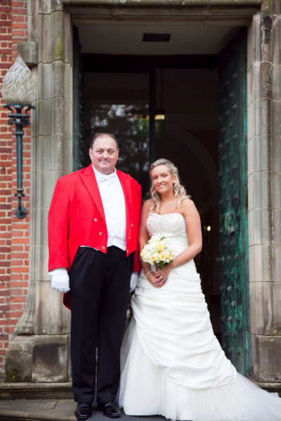 Nick Ede in his redcoat tails posing with the beautiful blushing bride in the doorway at Hartsfield Manor