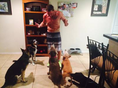 Shirtless dog trainer, lots of dogs