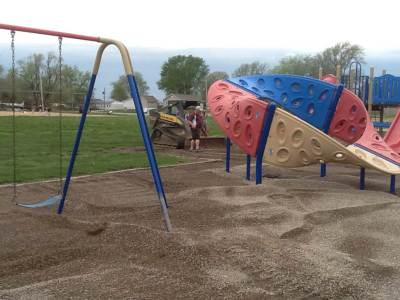 Spread gravel on playground area at Unity Elementary