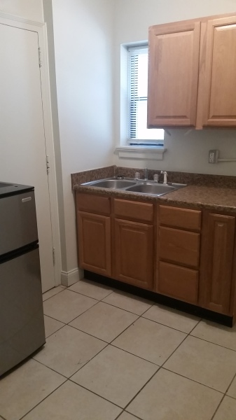 Tiled kitchen with updated counter tops and wooden cabinets