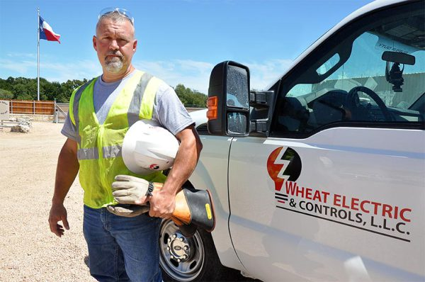Ed Wheat owner of Wheat Electric wearing working clothes