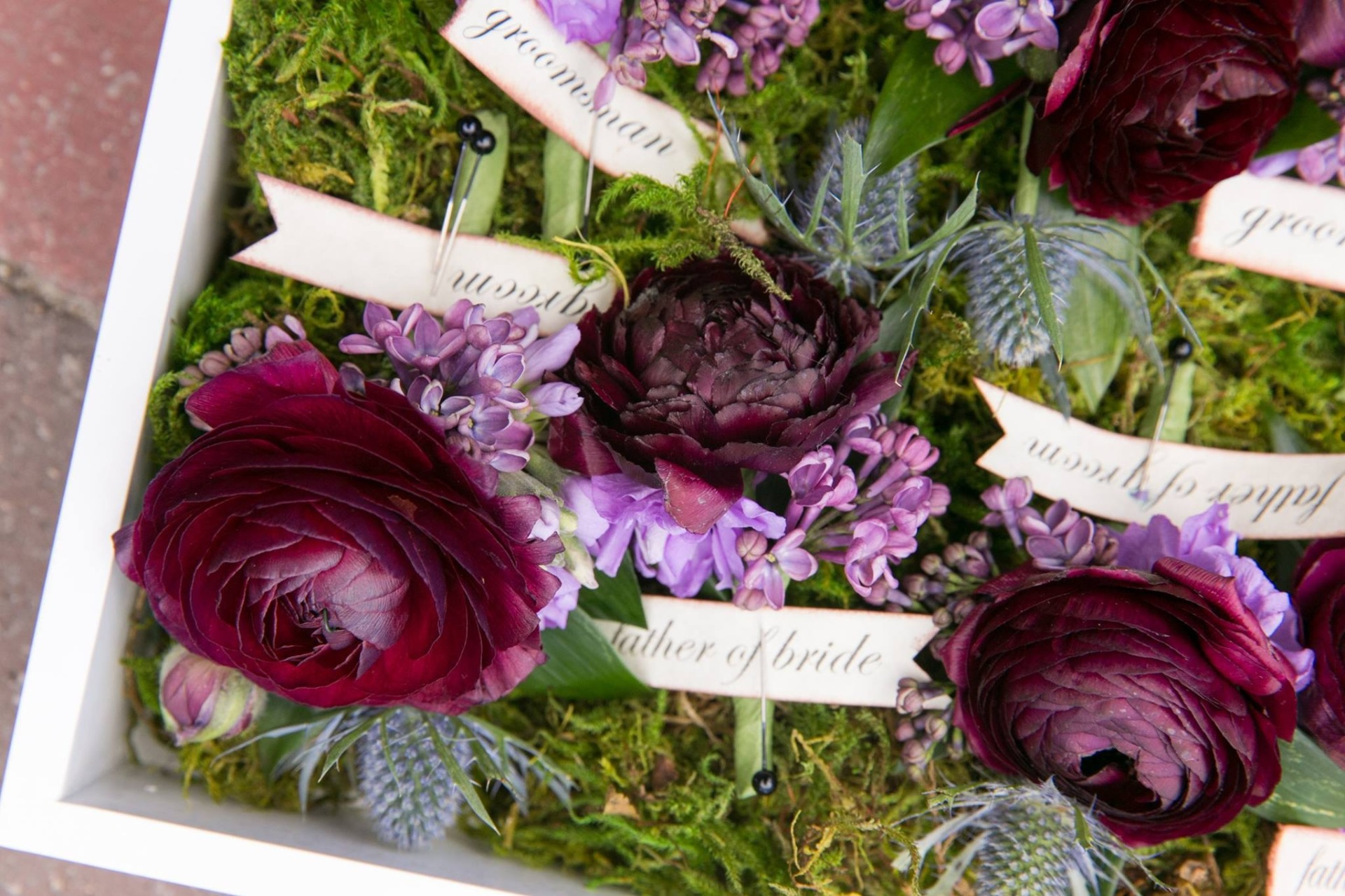 Sweet Boutonnieres featuring Ranunculus, lilac, thistle and greenery