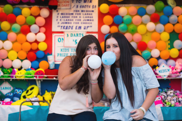 two senior girls blowing up balloons at the oklahoma state fair in oklahoma city oklahoma