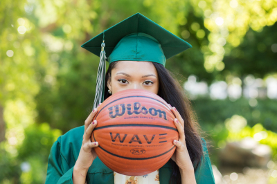 senior girl wearing green cap and gown holding basketball in oklahoma city oklahoma