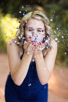 senior girl wearing blue blowing confetti in harrah oklahoma
