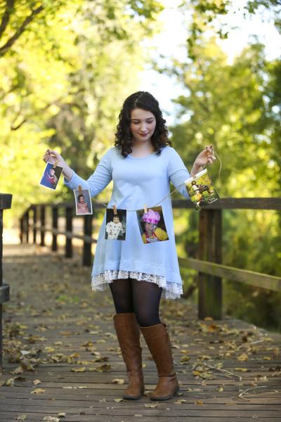 senior girl holding childhood photos while standing on bridge in oklahoma city oklahoma