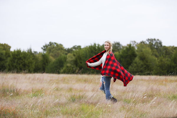 senior girl with red blanket standing in field in harrah oklahoma