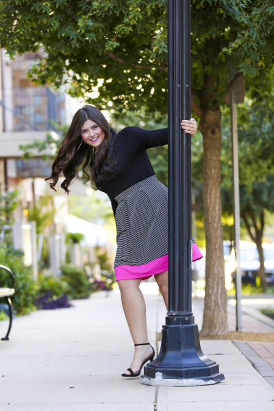 senior girl wearing skirt spinning around light post in downtown oklahoma city