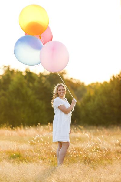 senior girl holding large balloons standing in field in harrah oklahoma
