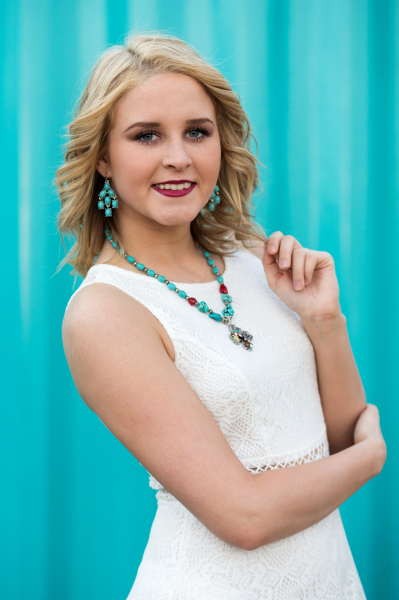 senior girl wearing white dress and blue necklace posing for camera in oklahoma city oklahoma