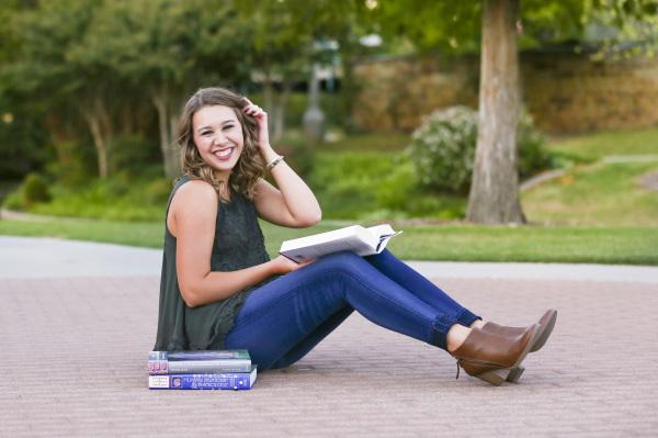 senior girl reading medical books while sitting on brick in bricktown oklahoma city oklahoma