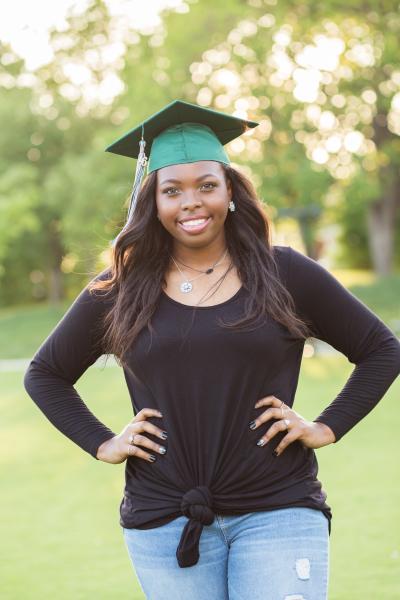 senior girl wearing green cap looking at camera at myriad gardens in oklahoma city oklahoma