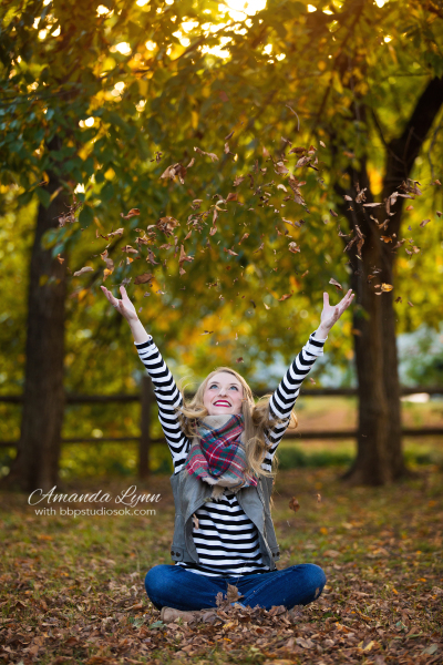 senior girl sitting on ground throwing leaves in the air in edmond oklahoma