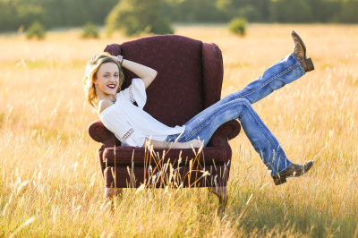 senior girl wearing jeans and boots sitting in red chair in a field in harrah oklahoma