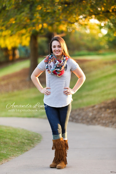 senior girl wearing large scarf posing for camera while standing on path in oklahoma city oklahoma