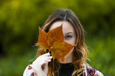 senior girl holding fall leaf in front of face at myriad gardens in oklahoma city oklahoma