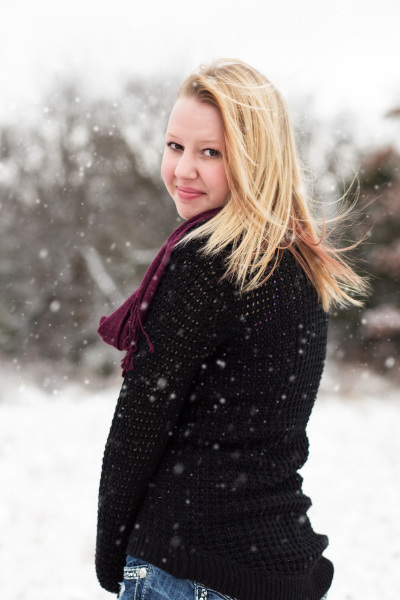 senior girl standing in snow looking back at camera in harrah oklahoma