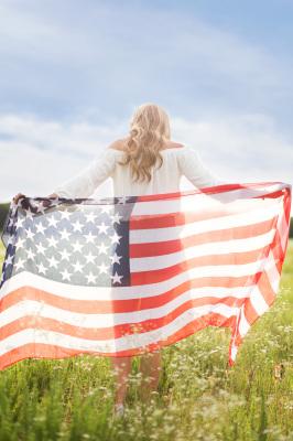 senior girl holding flag walking through field in harrah oklahoma