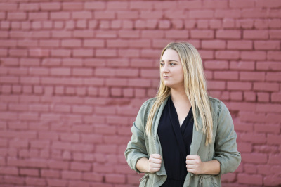 senior girl wearing green jacket standing in front of red brick wall in oklahoma city oklahoma