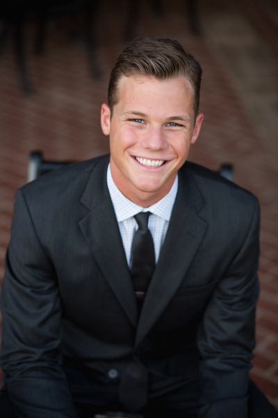 senior boy wearing suit sitting in chair in stillwater oklahoma
