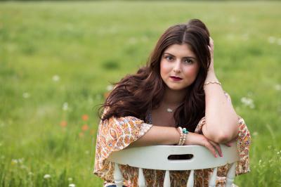 senior girl sitting in white chair in field in harrah oklahoma