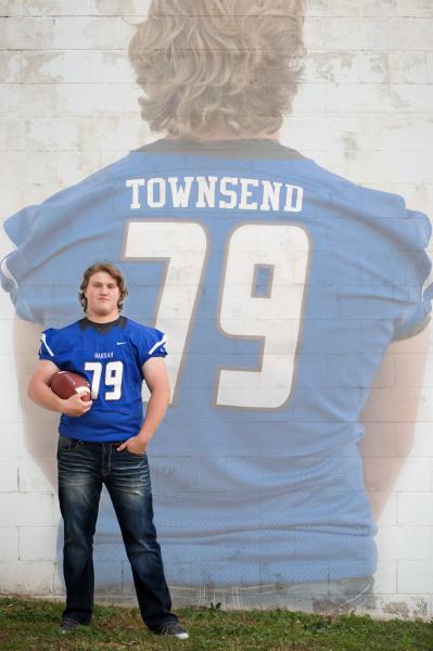 senior boy wearing blue football jersey holding football in harrah oklahoma