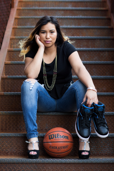 senior girl holding basketball shoes sitting on staircase in oklahoma city oklahoma