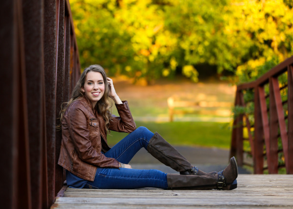 senior girl wearing jacket leaning on bridge in edmond oklahoma