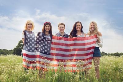 senior girl for rep program holding flag standing in field in harrah oklahoma