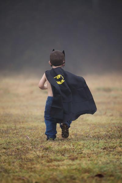little boy wearing bat man cape running through field in harrah oklahoma