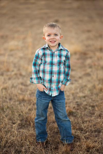 little boy wearing cowboy boots standing in field in stillwater oklahoma